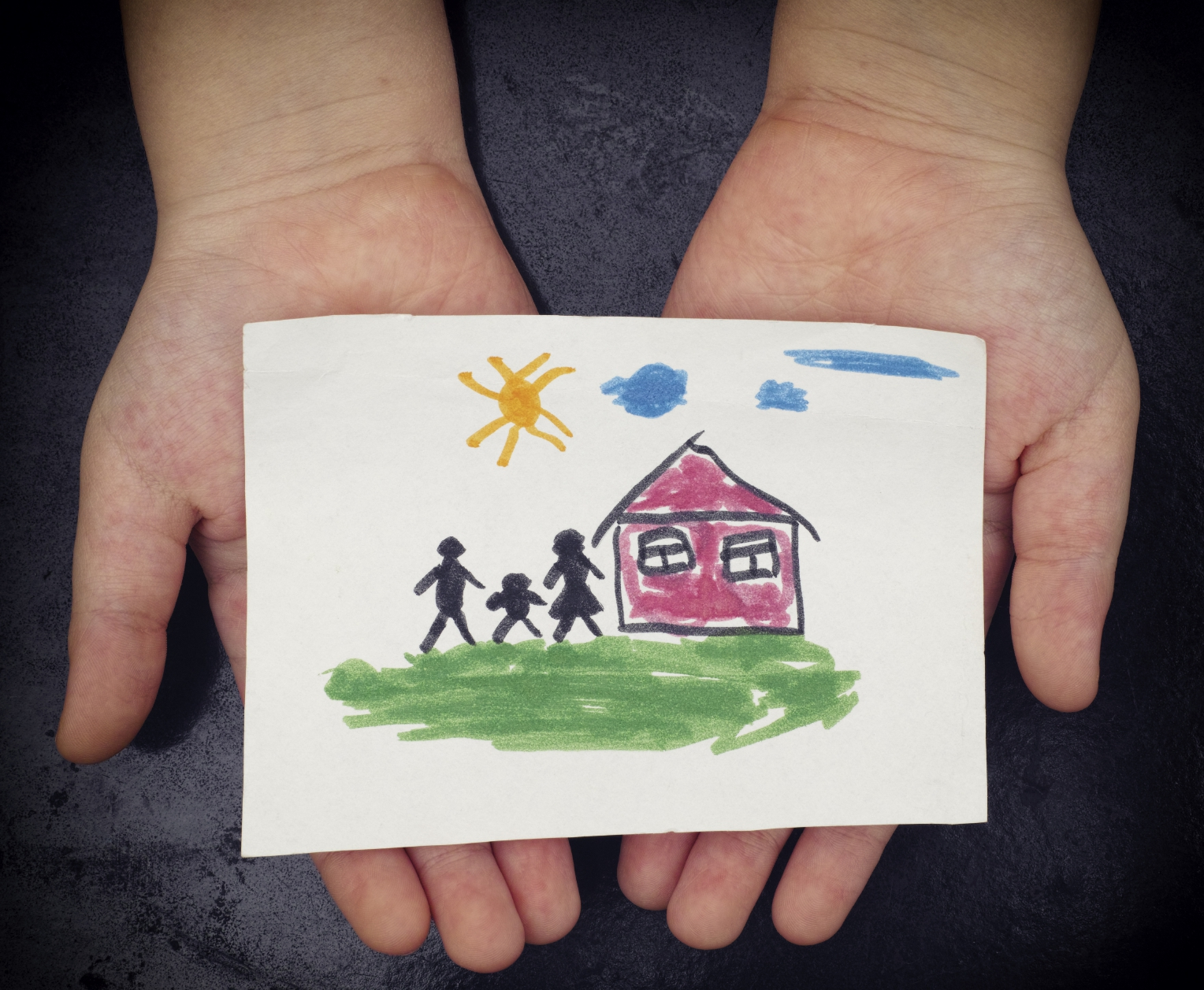 Child holds a drawn house with family. Close up. Vignette.