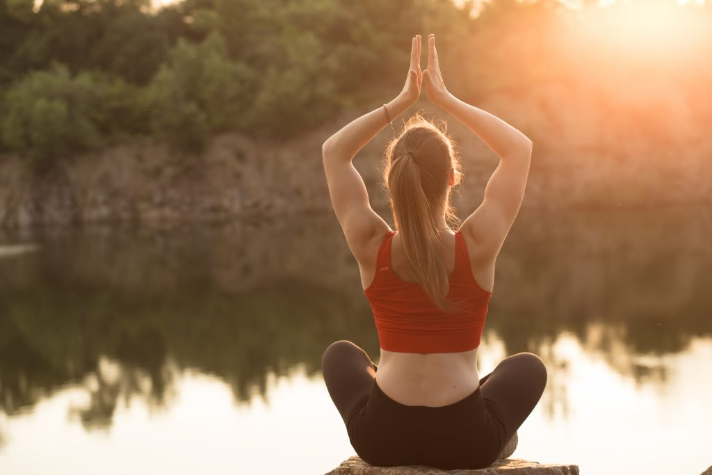 Sporty woman practicing yoga at sunset